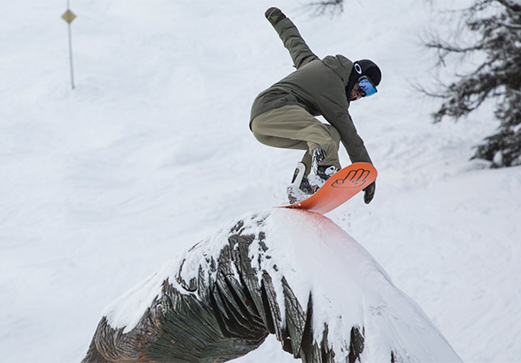 Snowboarder sliding on a wooden obstacle