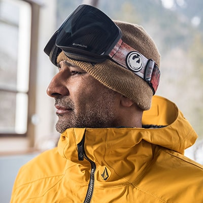 man looking to the side with snowboard goggles on his head