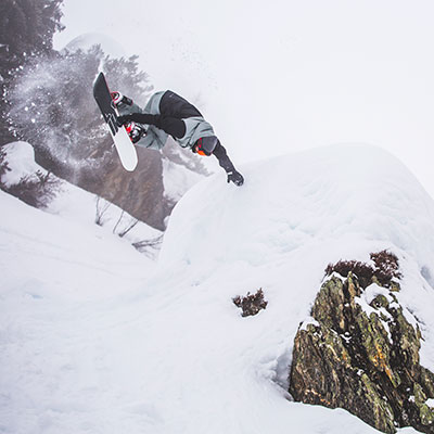 Snowboarder flipping over a hill