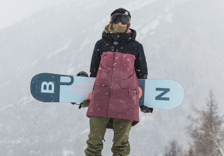 A snowboarder holding a snowboard