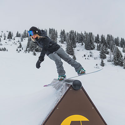 Snowboarder stalling on a barrier