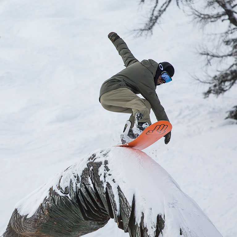 Snowboarder sliding on a wooden rail