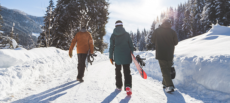 A group of snowboarders walking