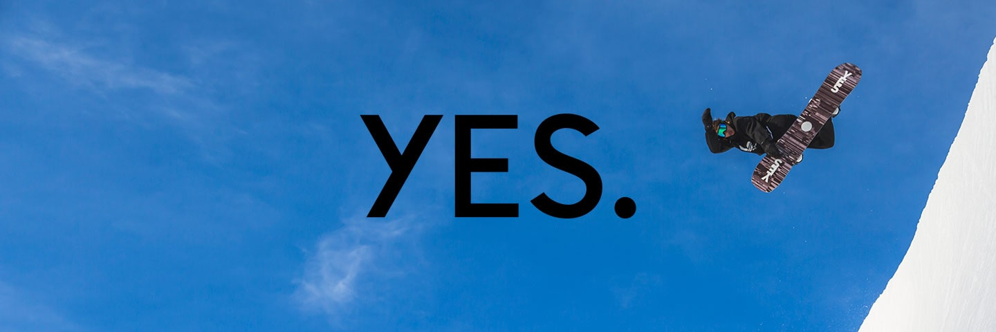 Yes logo with blue skies and snowboarder taking a jump in background