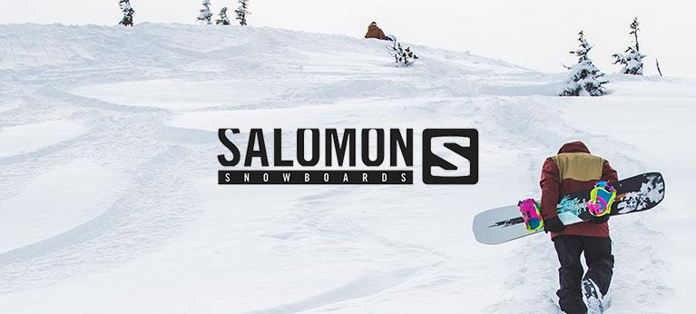 Salomon logo with snowboarder holding salomon snowboard in background