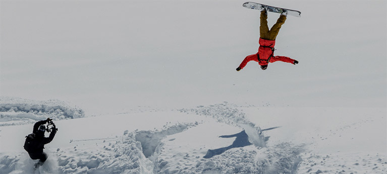 A snowboarder back flipping