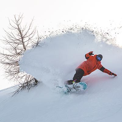 Snowboarder slashing snow