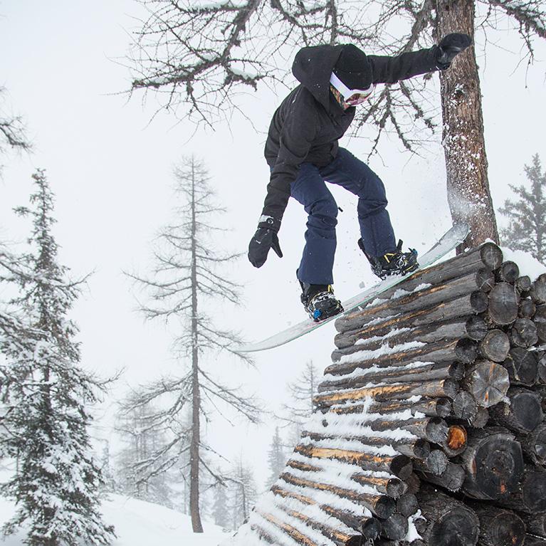 Man doing snowboard stall trick